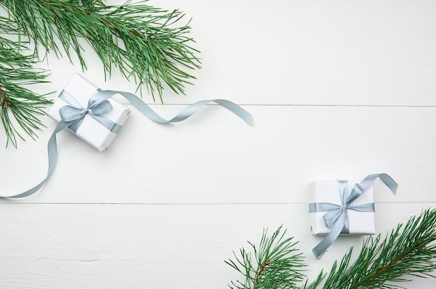 Weihnachtsgeschenkboxen mit kiefernzweigen auf weißem hintergrund