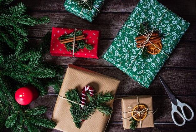 Weihnachtsgeschenkboxen mit kraft-, rot-, grünpapierdekoration, schere, kerze und tannenzweigen