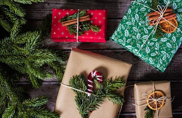 Weihnachtsgeschenkboxen mit kraft-, rot-, grünpapierdekoration und tannenzweigen