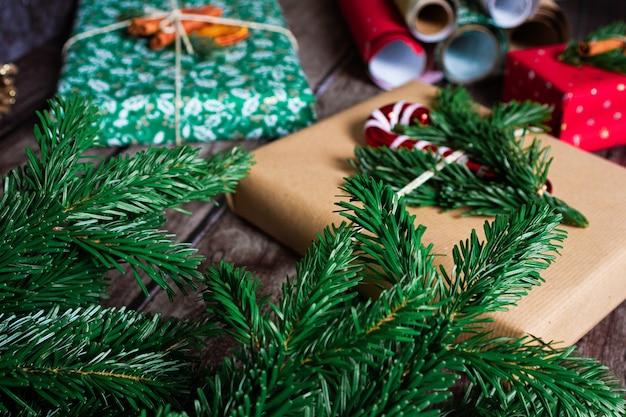 Weihnachtsgeschenkboxen mit kraft, roter, grüner dekoration, bunten papierrollen und tannenzweigen