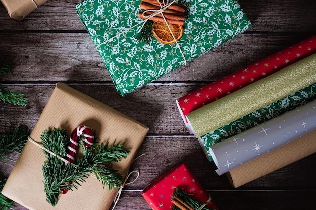 Weihnachtsgeschenkboxen mit kraft, roter, grüner dekoration und bunten papierrollen