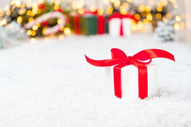 Weihnachtsgeschenkboxen mit rotem band und bogen auf dem schnee mit verschwommenen lichtern