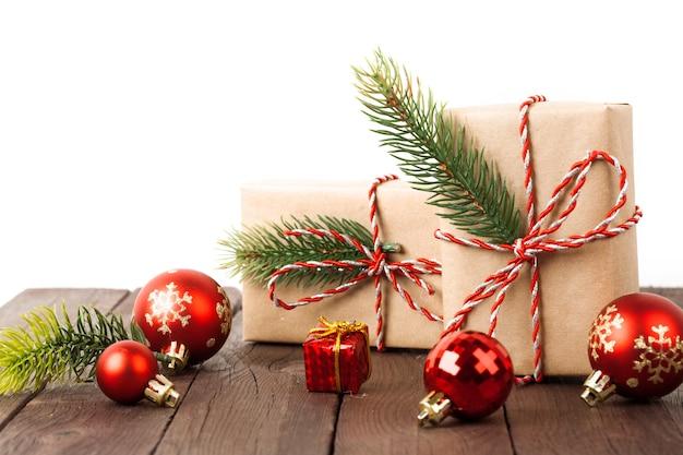 Weihnachtsgeschenkboxen mit weihnachtskugeln auf holztisch