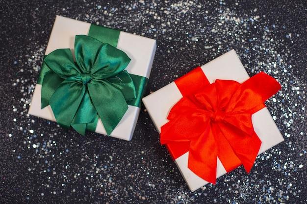 Weihnachtsgeschenkboxen oder geschenk mit schleifenband auf magischem silberglitter auf schwarzem hintergrund.