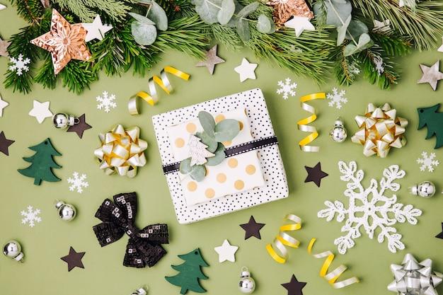 Weihnachtsgeschenkboxen und dekorationen in den farben grün und schwarz. flache lage, ansicht von oben