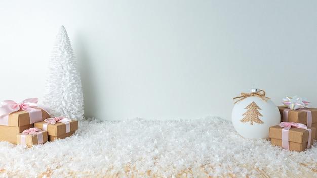 Weihnachtsgeschenkboxen und kugeldekoration auf schnee