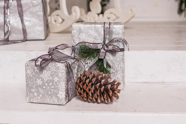 Weihnachtsgeschenkboxen und silberbögen auf weißem hintergrund. feiertagsgrußkarte. eingewickelte geschenkboxen. neujahrsfeiertage. handgemachte geschenke