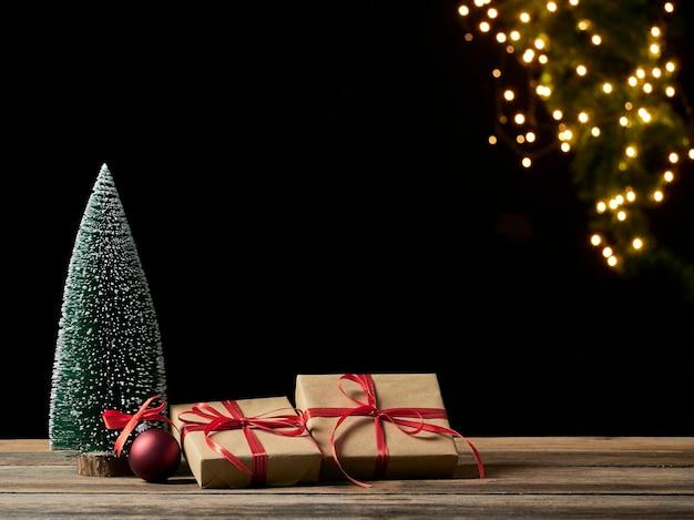 Weihnachtsgeschenkboxen und tannenbaum auf holztisch gegen unscharfe festliche lichter, platz für text