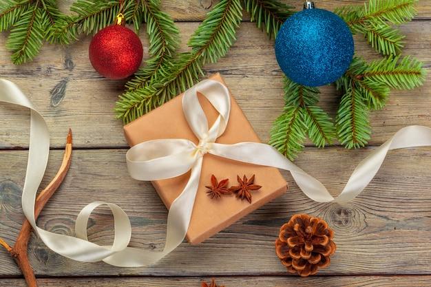 Weihnachtsgeschenkboxen und tannenbaumast auf holztisch.