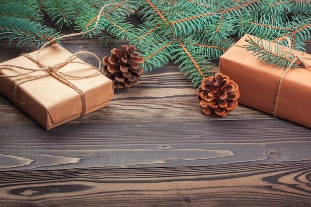 Weihnachtsgeschenkboxen und tannenzweig auf holztisch,