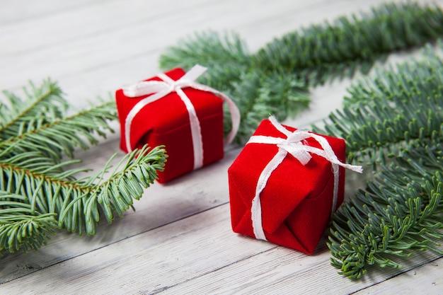 Weihnachtsgeschenkboxen und tannenzweige auf einem hölzernen hintergrund, das konzept der feier des neuen jahres