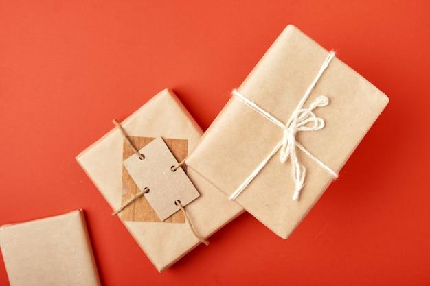 Weihnachtsgeschenkboxen verpackt in kraftpapier mit dekoration auf rotem hintergrund draufsicht