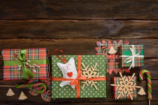 Weihnachtsgeschenkboxen verziert mit buntem papier und bändern auf dem holztisch