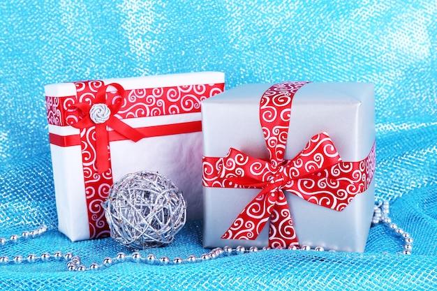 Weihnachtsgeschenkboxen verziert mit rotem band auf blauer stoffoberfläche