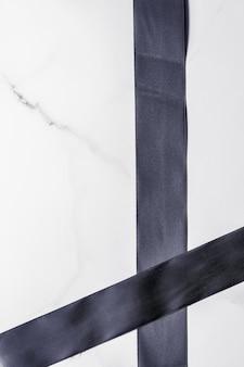 Weihnachtsgeschenkdekoration und verkaufsförderungskonzept schwarzes seidenband und bogen auf marmorhintergrund flatlay