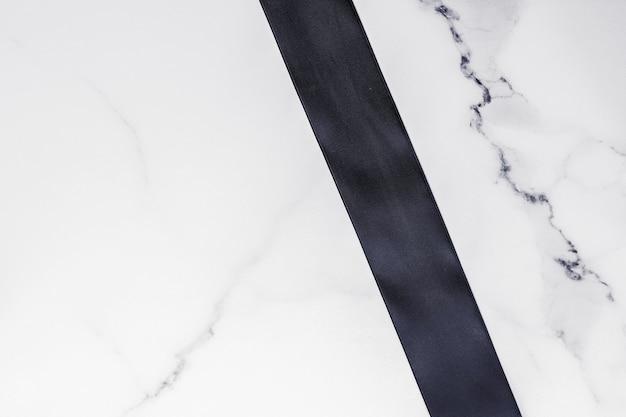 Weihnachtsgeschenkdekoration und verkaufsförderungskonzept schwarzes seidenband und schleife auf marmorhintergrund f...