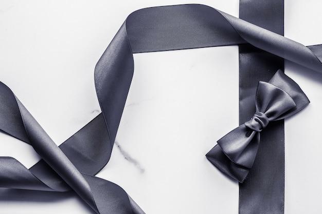 Weihnachtsgeschenkdekoration und verkaufsförderungskonzept schwarzes seidenband und schleife auf marmorhintergrund f... Premium Fotos