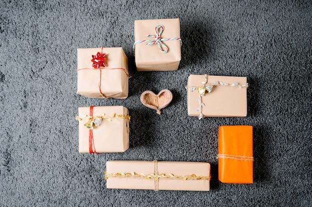 Weihnachtsgeschenke angeordnet in einem kreis auf einem hölzernen herzen