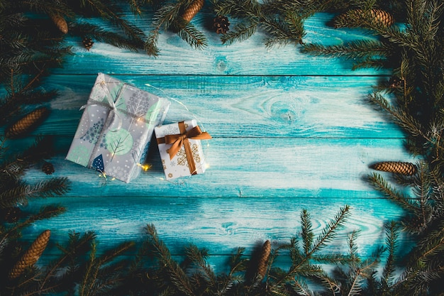 Weihnachtsgeschenke auf blauem holztisch mit tannenzweigen und weihnachtslichtern.