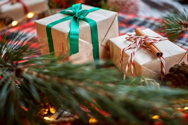 Weihnachtsgeschenke auf dem hintergrund eines roten karierten wollplaids mit girlanden von zapfen und tannenzweigen