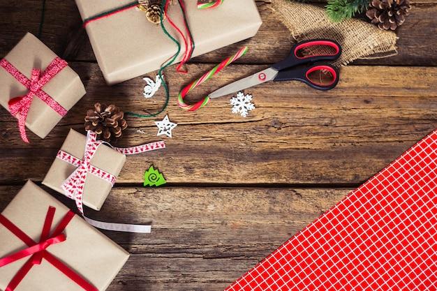 Weihnachtsgeschenke auf einem hölzernen hintergrund mit zuckerstange, tannenzweigen, kerze, kegel.