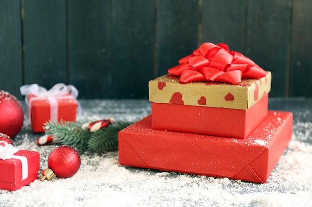 Weihnachtsgeschenke auf farbigem holzhintergrund