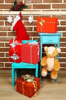 Weihnachtsgeschenke auf stuhl auf braunem backsteinmauerhintergrund