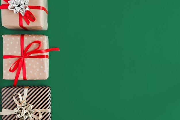 Weihnachtsgeschenke eingewickelt in kraftpapier mit roten und gelben bändern auf grünem hintergrund
