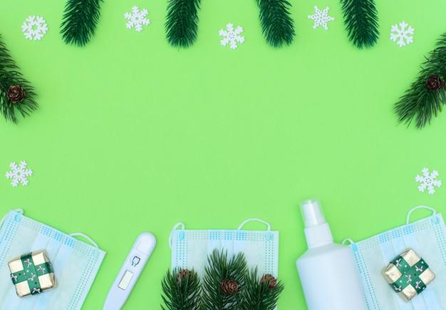 Weihnachtsgeschenke, fichte mit tannenzapfen, medizinische masken, thermometer, desinfektionsmittel auf grünem hintergrund.