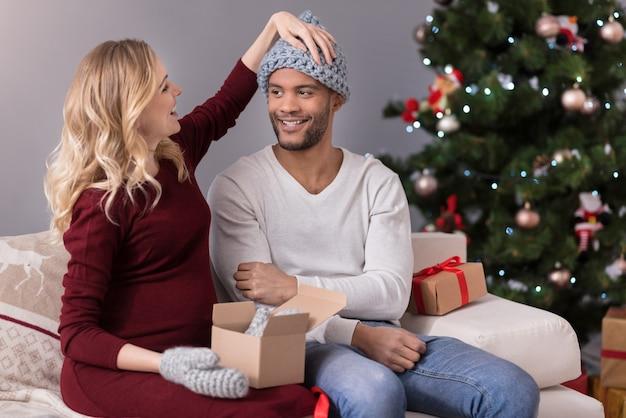 Weihnachtsgeschenke. freudige schöne entzückte frau, die auf dem sofa sitzt und ihren ehemann ansieht, während sie ihm hilft, einen warmen hut aufzusetzen