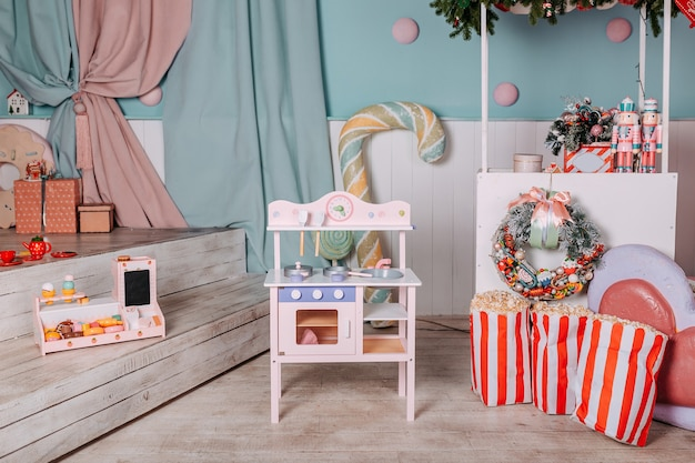Weihnachtsgeschenke für kinder unter dem baum. spielzeugküchengeschenk für mädchen. weihnachtsgeschenk unter dem baum. spielzeug holzküche und geschirr.