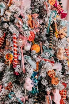 Weihnachtsgeschenke für kinder unter dem baum. weihnachtsbaum mit spielzeug und bunten zuckerstangen und süßigkeiten geschmückt. präsentieren sie kisten unter dem weihnachtsbaum.