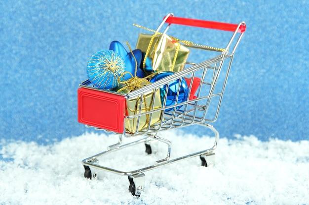 Weihnachtsgeschenke im einkaufswagen, auf blauem glänzendem hintergrund