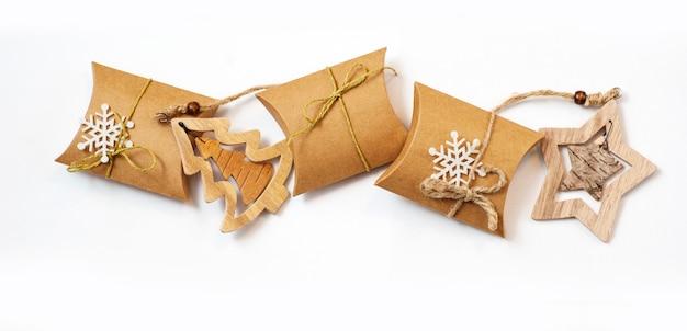 Weihnachtsgeschenke im kraftpapier mit selbst gemachte spielwaren auf weiß