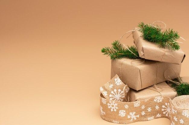 Weihnachtsgeschenke in bastelpapier eingewickelt, verziert mit tannenzweigen und leinenband.