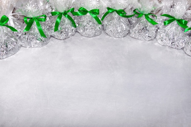 Weihnachtsgeschenke in form von folienbeuteln und transparenter folie, die mit einem bogen von einem grünen band gebunden werden, auf dem schneeflocken auf einem grauen hintergrund sind.