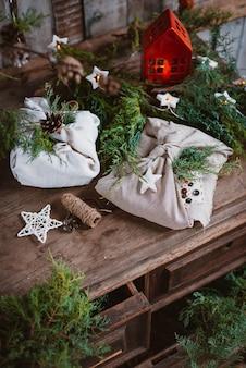 Weihnachtsgeschenke in furoshiki-stoff im japanischen stil in nadel- und fichtenzweigen eingewickelt. vorbereitung und gestaltung der neujahrsferien. rustikaler stil handgemacht, ideen billig