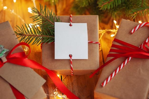 Weihnachtsgeschenke in handwerksverpackung auf einem holztisch vor dem hintergrund eines geschmückten weihnachtsbaumes.