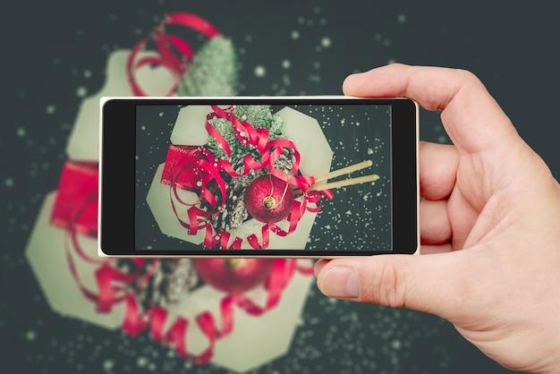 Weihnachtsgeschenke in wok-papierverpackungsboxen auf dem smartphonebildschirm.