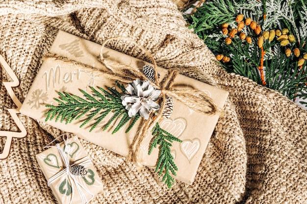 Weihnachtsgeschenke mit geschenkbox verziert mit tannenzapfen und zweigen auf einem baumwollstoff
