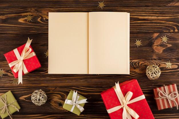 Weihnachtsgeschenke mit leerem buch auf holztisch