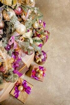 Weihnachtsgeschenke mit purpurroter, goldener dekoration, geschenke. weihnachtsdekoration. lila geschenkboxen unter weihnachtsbaum