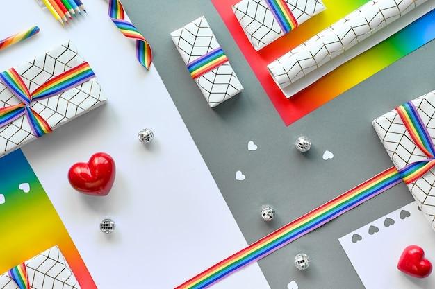 Weihnachtsgeschenke mit regenbogenband in den lgbt-gemeinschaftsflaggenfarben. flach auf zweifarbigem papier liegen