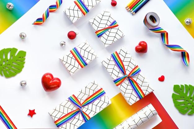 Weihnachtsgeschenke mit regenbogenband in lgbtq-gemeinschaftsflaggenfarben gebunden. flach lag mit weihnachtsdekor.