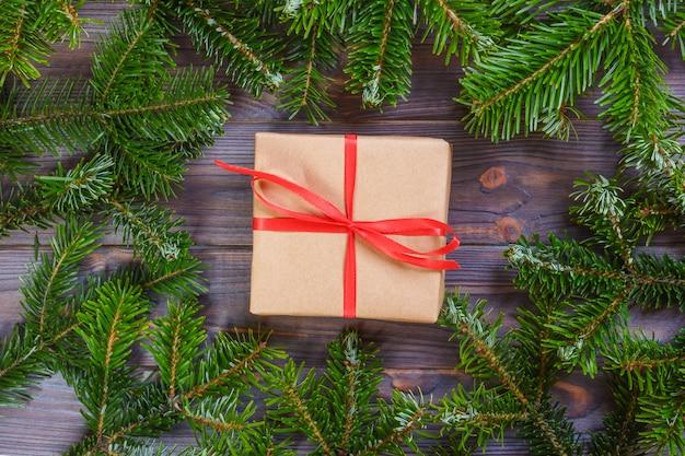 Weihnachtsgeschenke mit rotem band auf dunklem hölzernem hintergrund in einem rahmen gemacht von den tannenzweigen mit stöcken. flacher laienstil