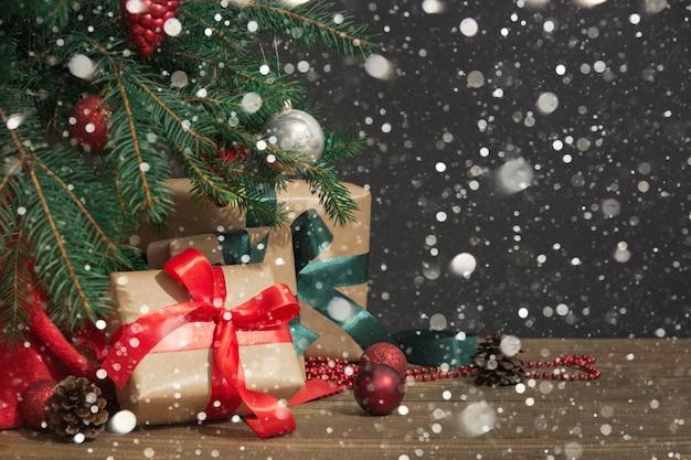 Weihnachtsgeschenke mit rotem band, sankt hut und dekor unter weihnachtsbaum.