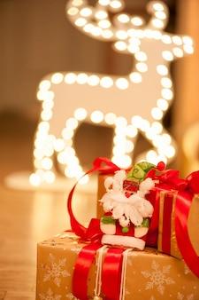 Weihnachtsgeschenke mit santa claus auf einem hintergrund von girlanden in form eines rotwilds