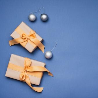 Weihnachtsgeschenke mit silbernen kugeln auf blauem hintergrund