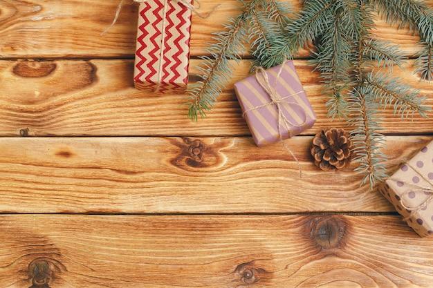 Weihnachtsgeschenke mit tannenbaumasten auf hölzernem hintergrund