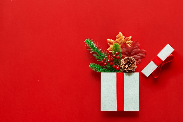 Weihnachtsgeschenke präsentiert papierkunst auf rotem grund mit festlichen feiertagsdekorationen, blätter, tannenzweigen, tannenzapfen,